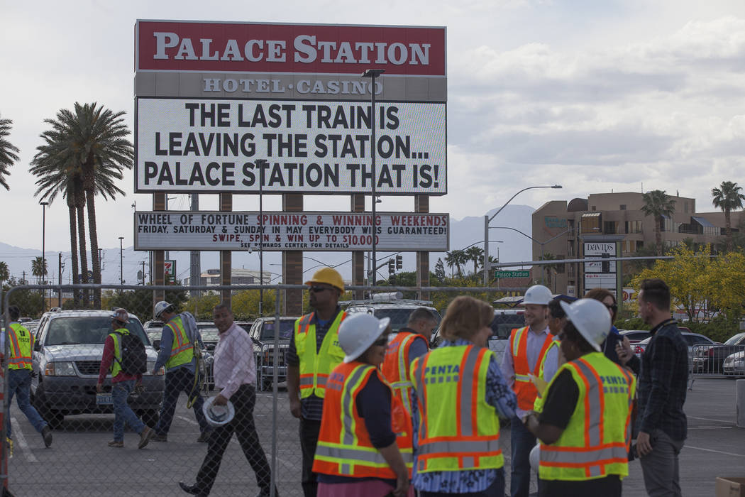 Workers and media leave the parking lot where the top piece of Palace StationÕs train sign rests in the parking lot in Las Vegas, Monday, April 30, 2018. The marquee is the final train-themed ...
