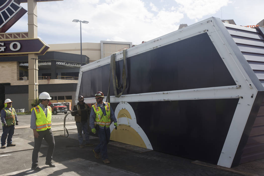 Workers walk past the top piece of Palace Station's train sign in the parking lot in Las Vegas, Monday, April 30, 2018. The marquee is the final train-themed remnant of the Station Casinos' ...