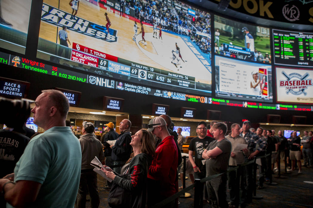 Sports betters line up to place their bets as games play overhead on giant screens at the Superbook at Westgate in Las Vegas on Thursday, March 15, 2018. Patrick Connolly Las Vegas Review-Journal ...
