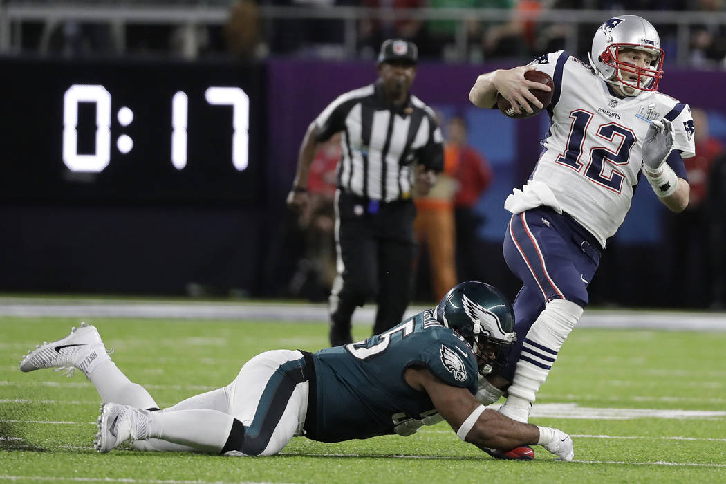 New England Patriots' Tom Brady (12) runs from Philadelphia Eagles' Brandon Graham during the first half of the NFL Super Bowl 52 football game Sunday, Feb. 4, 2018, in Minneapolis. (AP Photo/Mark ...