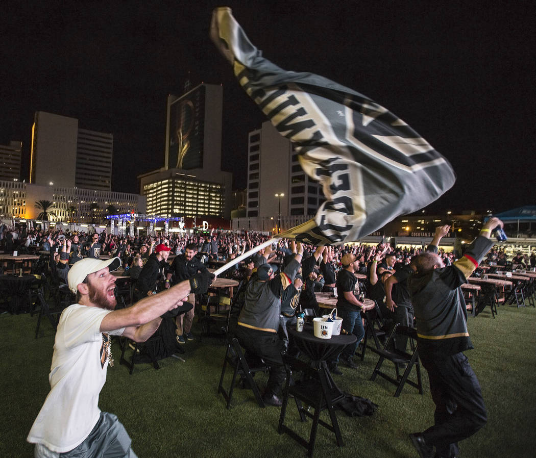 Golden Knights fan Matt Helfst, left, erupts after a second period goal at a watch party during game three of Vegas' playoff series with the San Jose Sharks on Monday, April 30, 2018, at Downtown ...
