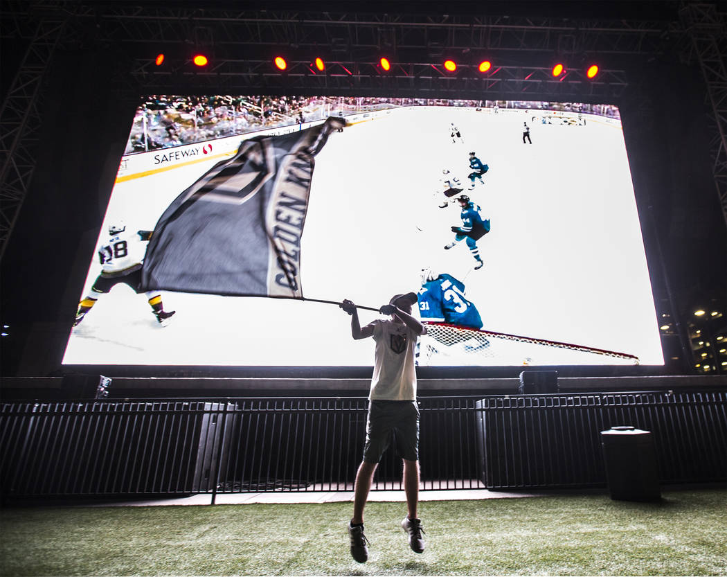 Golden Knights fan Matt Helfst waves his team's flag after a second period goal at a watch party during game three of Vegas' playoff series with the San Jose Sharks on Monday, April 30, 2018, at D ...