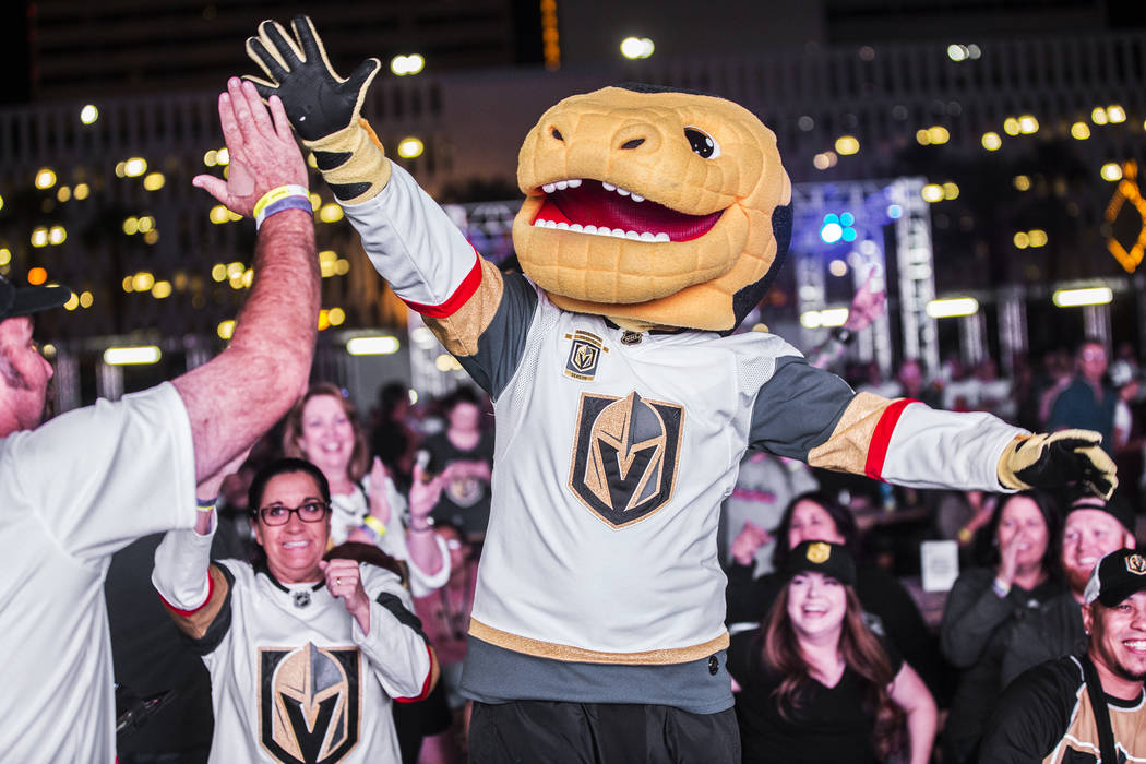 Golden Knights mascot Chance, right, celebrates with fan Bernie Lange after a second period goal at a watch party during game three of Vegas' playoff series with the San Jose Sharks on Monday, Ap ...