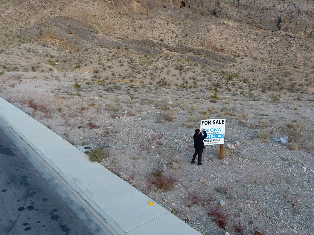 Property developer, Andy Pham, removes a For Sale sign from his property that was placed on after it was allegedly stolen using the Nevada secretary of state web site on Wednesday, March 28, 2018. ...
