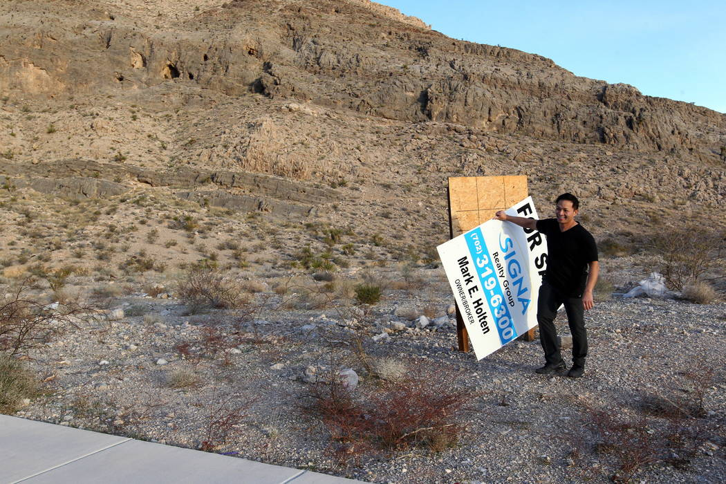 "Real estate investor Andy Pham removes a fraudulent ""for sale"" sign on his northwest Las Vegas property Jan. 30, 2018. Pham and his investors lost control of the multi-million dollar pro ..."