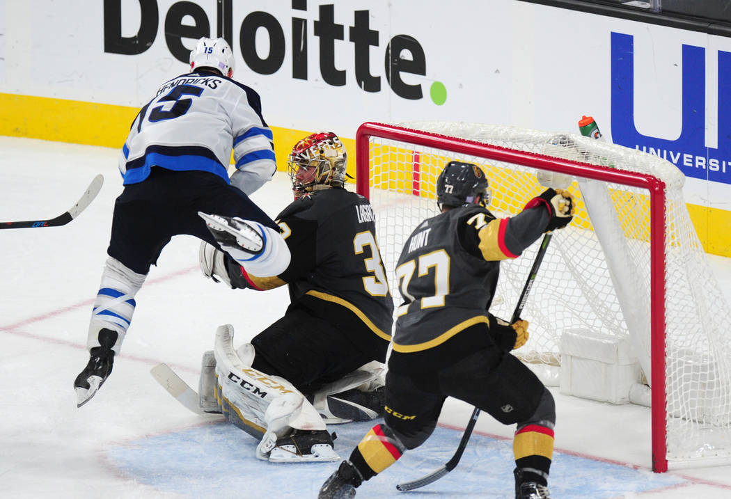 Winnipeg Jets forward Matt Hendricks (15) jumps to avoid contact with Vegas Golden Knights goalie Maxime Lagace in the third period of their NHL hockey game at T-Mobile Arena in Las Vegas Friday N ...