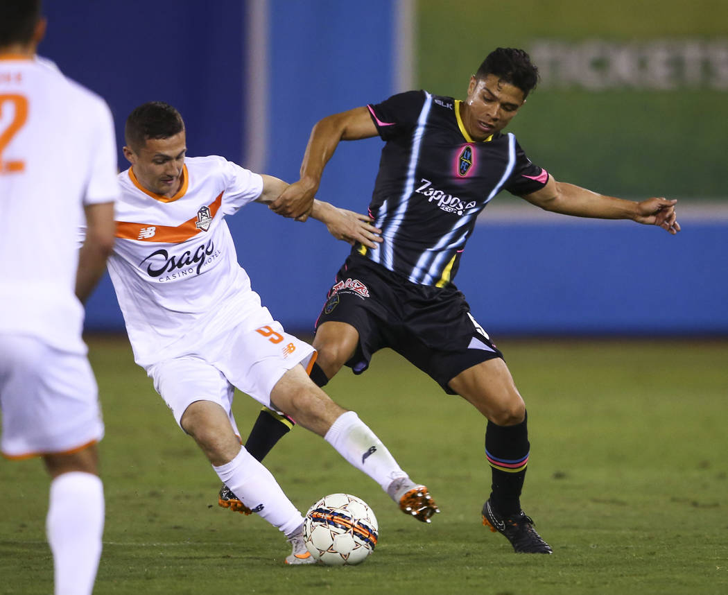 Las Vegas Lights FC defender Jorge Guillen-Torres (5) battles for the ball against Tulsa Roughnecks FC midfielder Michael Gamble (9) during the second half of a United Soccer League game at Cashma ...