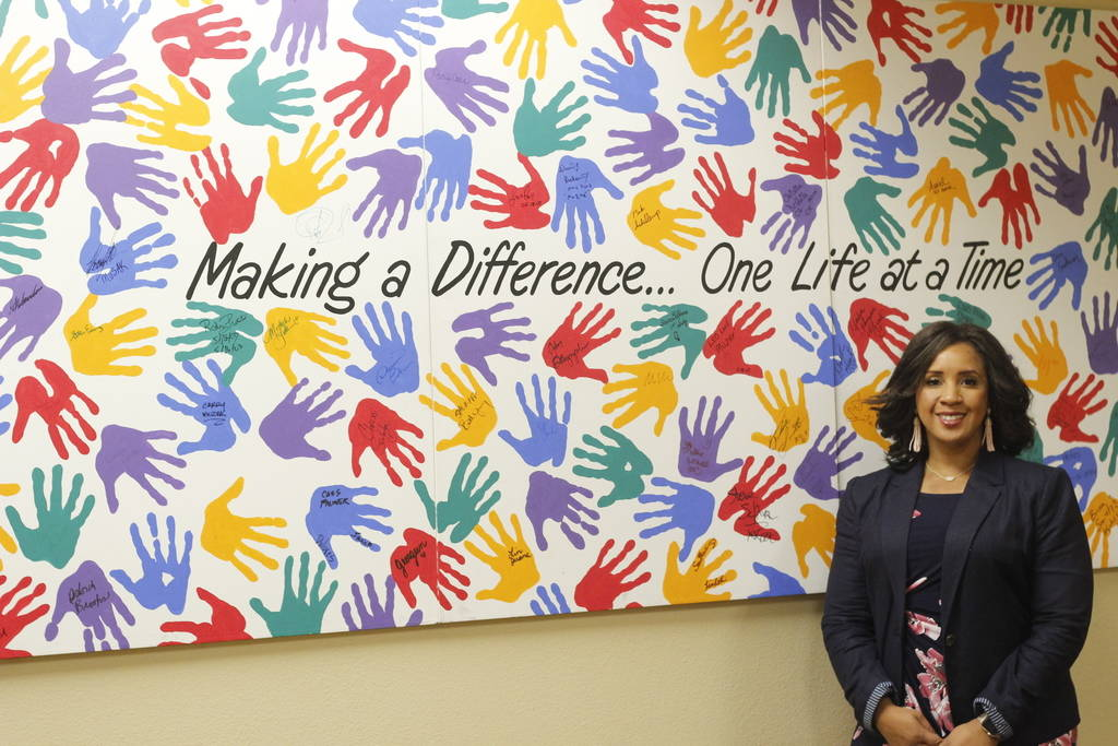 Myesha Wilson, executive director of Olive Crest, stands in front of a sign at Olive Crest on Wednesday, April 27, 2018. Wilson has worked as an advocate for at-risk children for over 15 years.