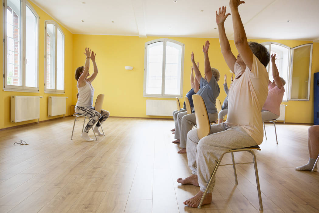 Teacher and active senior women yoga class on chairs. Getty Images