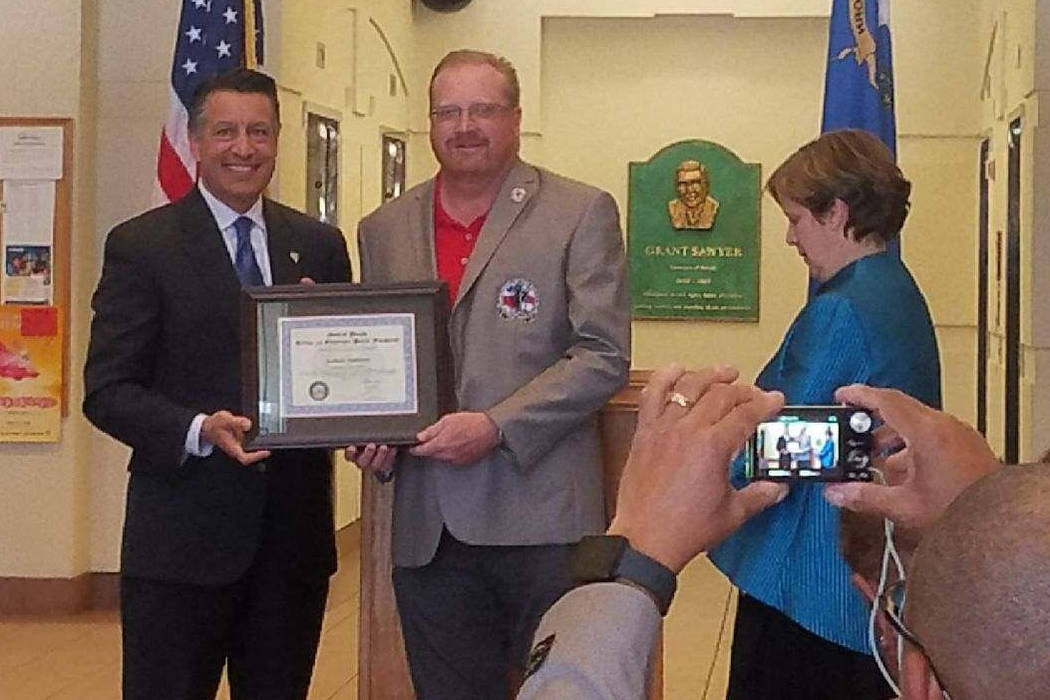 Rob Jackson (right) accepts the Veteran of the Month Award for April from Nevada governor Brian Sandoval. Courtesy photo.