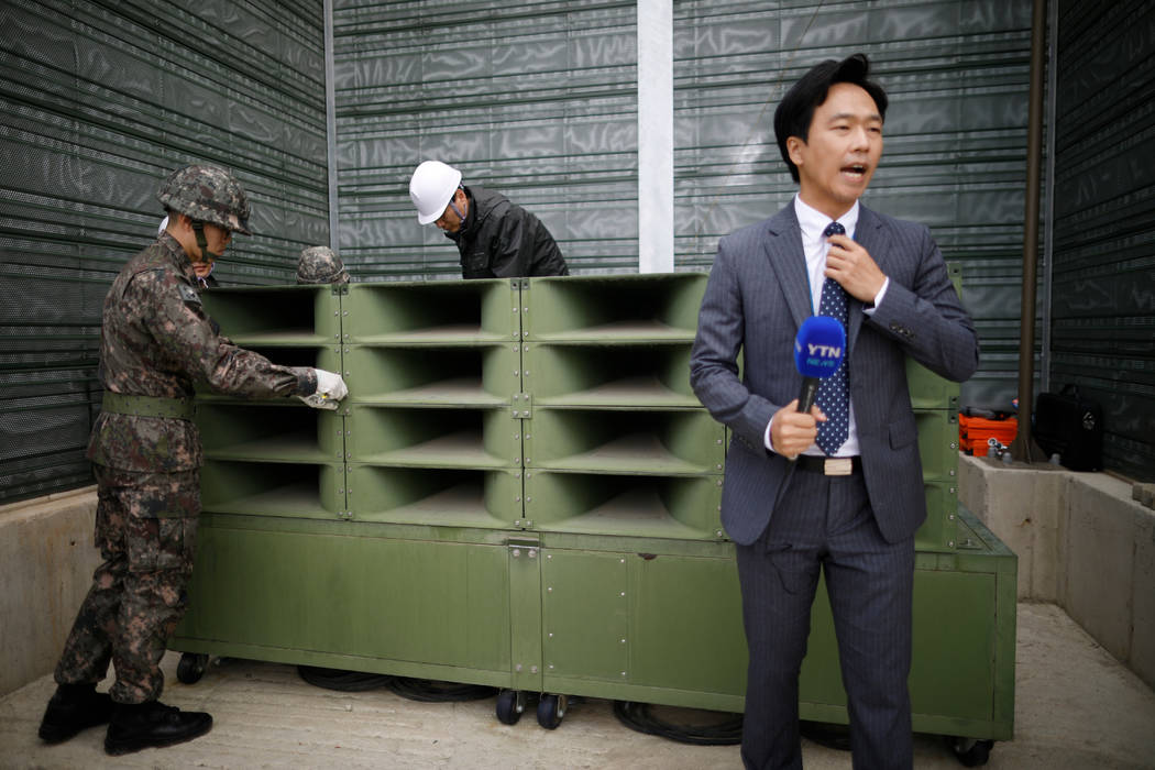 A reporter prepares a news report as South Korean soldiers dismantle loudspeakers that used to broadcast propaganda near the Demilitarized Zone separating the two Koreas in Paju, South Korea, Tues ...
