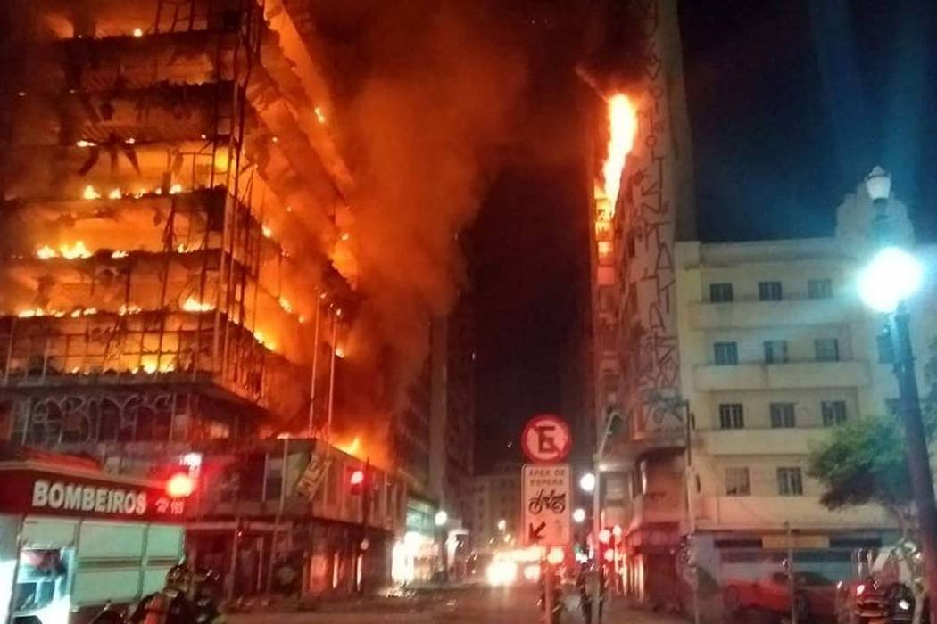 In this photo released by Sao Paulo Fire Department, a building on fire is seen in Sao Paulo, Brazil, Tuesday, May 1, 2018. A burning building in downtown Sao Paulo has collapsed as firefighters w ...