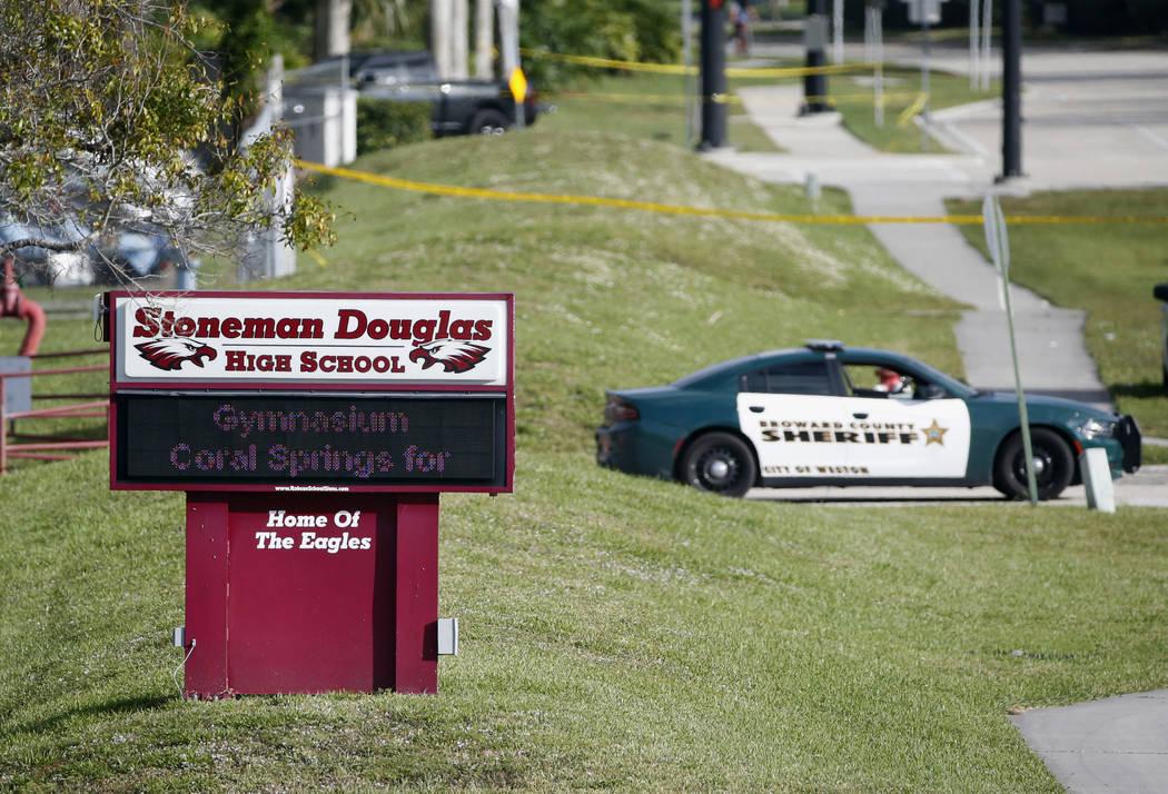Law enforcement officers block off the entrance to Marjory Stoneman Douglas High School, in Parkland, Fla. (Wilfredo Lee/AP)