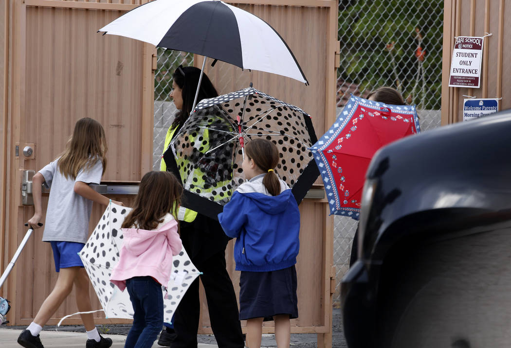 First-grade teacher Shereen Sayegh watches as students arrive at St. Viator Elementary School on a rainy morning on Tuesday, May 1, 2018, in Las Vegas. Tuesday shows a forecast high of 69 degrees, ...