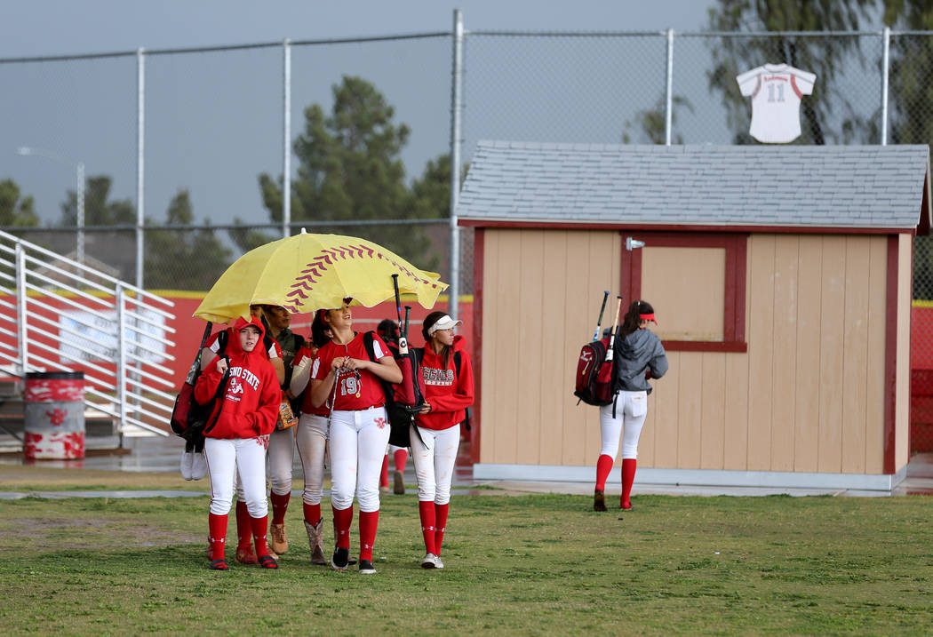 Members of the Arbor View varsity softball team share an umbrella after their game was cancelled due to rain at Arbor View High School in Las Vegas Tuesday, May 1, 2018. K.M. Cannon Las Vegas Revi ...