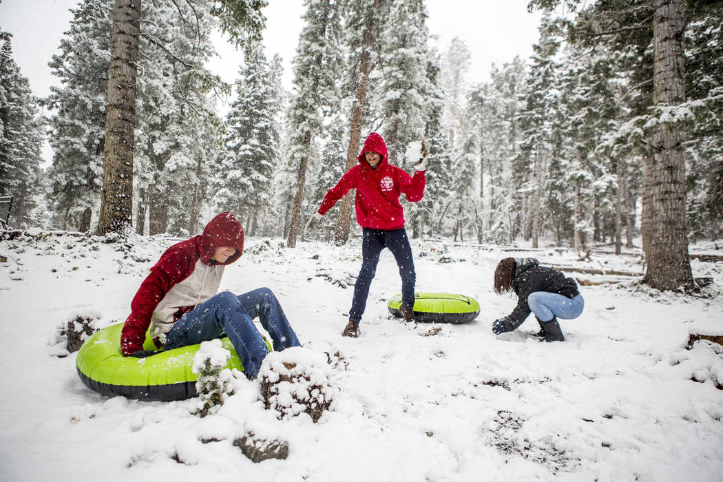 Zack Schneider looks to throw a snowball at his brother, Jeff Schneider, while Cassea Overton, right, prepares a snowball near the Cathedral Rock trailhead at Mount Charleston on Tuesday, May 1, 2 ...