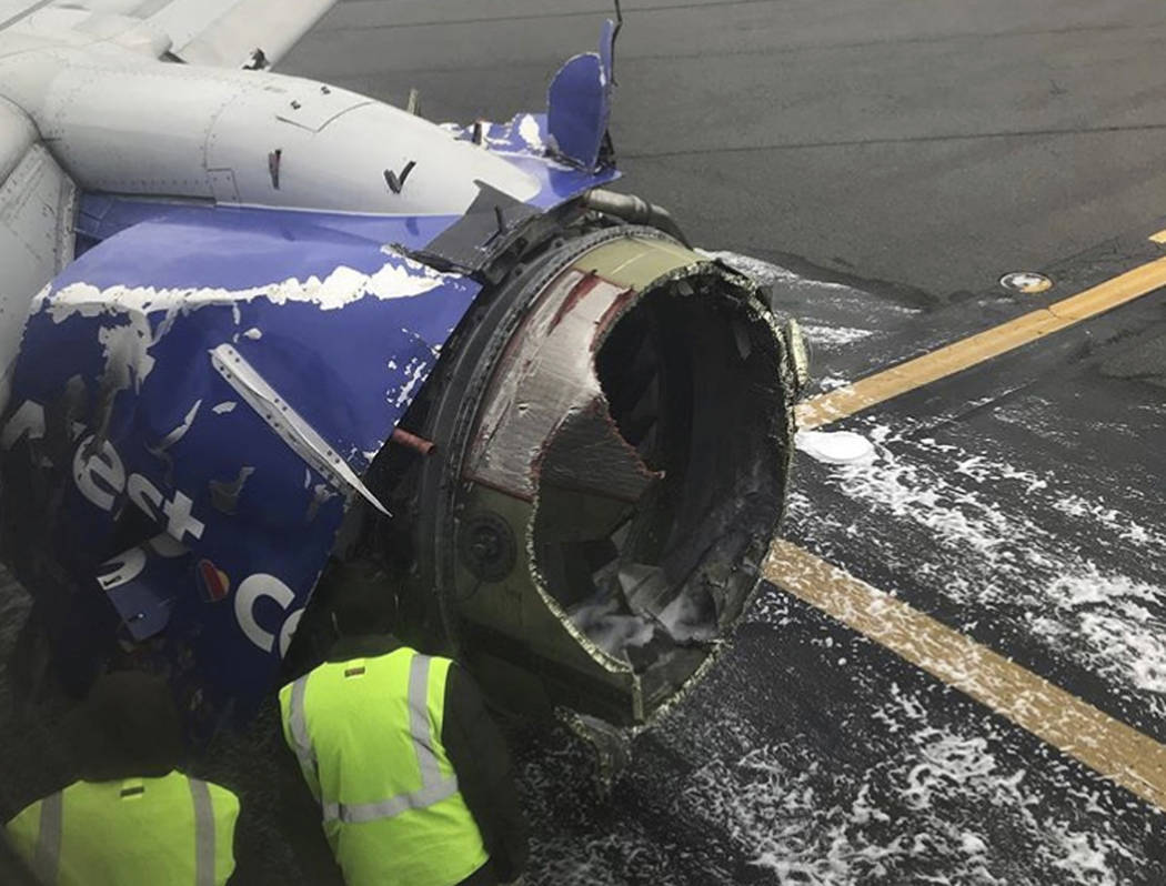 The engine on a Southwest Airlines plane is inspected as it sits on the runway at the Philadelphia International Airport after it made an emergency landing in Philadelphia, Tuesday, April 17, 2018 ...
