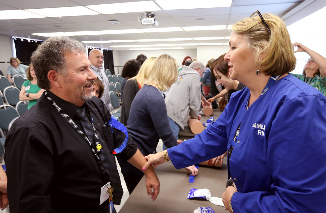 "Las Vegas Academy music teacher Tony Branco learns how to apply a tourniquet with Kay Godby during University Medical Center ""Stop the Bleed"" training at the school Monday, April 30, 201 ..."