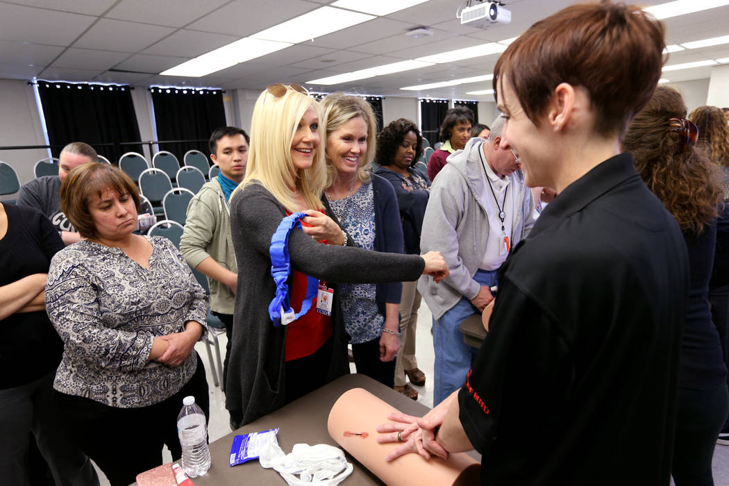 "Las Vegas Academy Dance Instructional Assistant Brandi Nelson, center, learns how to apply a tourniquet with Brandy Castillo during University Medical Center ""Stop the Bleed"" training at ..."