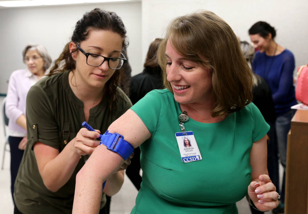 "Las Vegas Academy English teacher Haley Ruzek, left, practices applying a tourniquet on Assistant Principal Jennifer Shuler during University Medical Center ""Stop the Bleed"" training at ..."