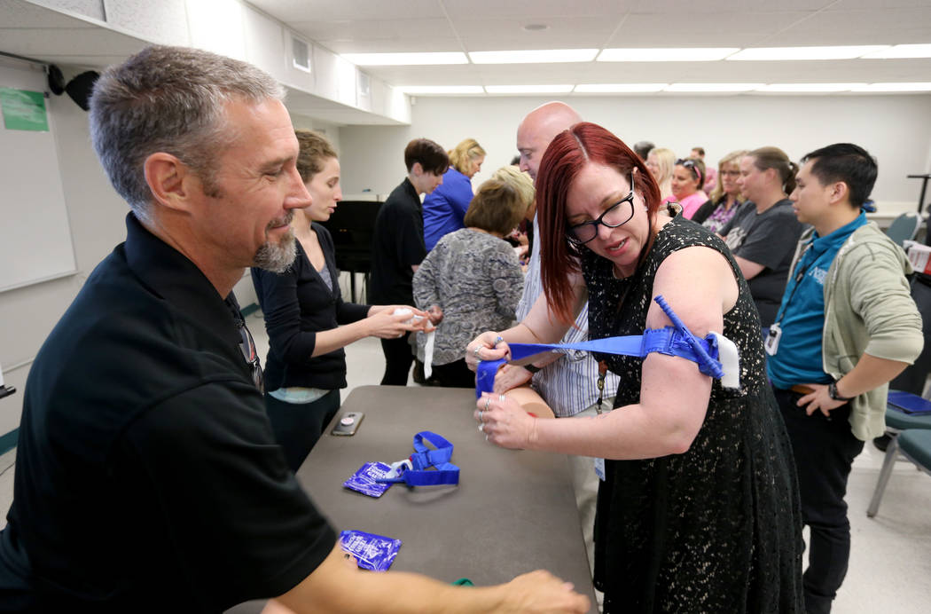 "Las Vegas Academy biology and careers teacher Eva Williams learns how to apply a tourniquet with John Maholick during University Medical Center ""Stop the Bleed"" training at the school Mo ..."