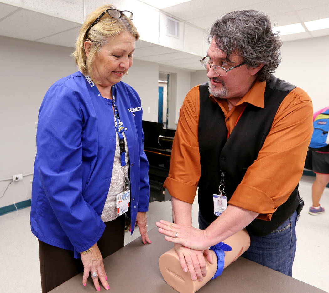 "Las Vegas Academy film production and visual arts instructor Sim Dulaney, right, learns how to apply a pressure to a wound with Kay Godby during University Medical Center ""Stop the Bleed&quot ..."