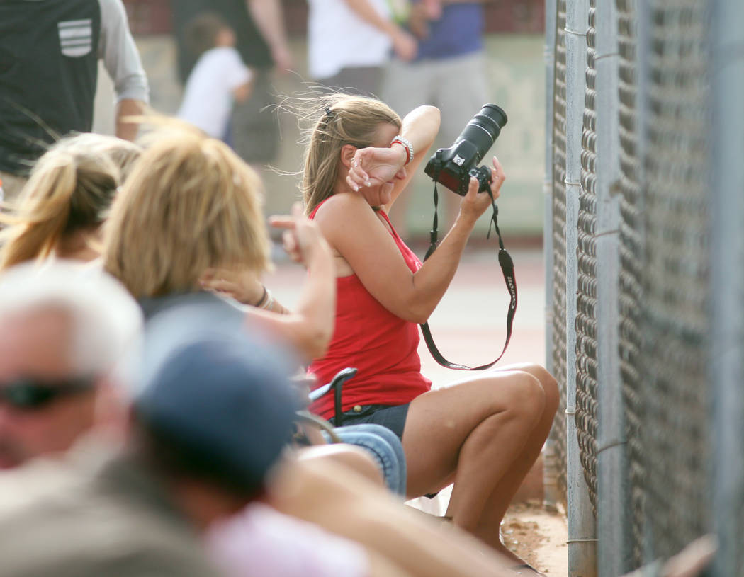 Arbor View baseball mom Susie Quintana, right, shields herself from the wind while taking photographs during an Arbor View boys baseball game against Cimarron-Memorial at Cimarron-Memorial High Sc ...