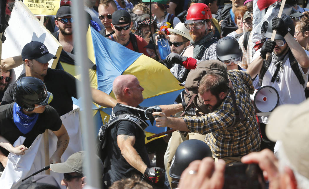 White nationalist demonstrators clash with counter demonstrators at the entrance to Lee Park in Charlottesville, Va., Saturday, Aug. 12, 2017. Gov. Terry McAuliffe declared a state of emergency a ...