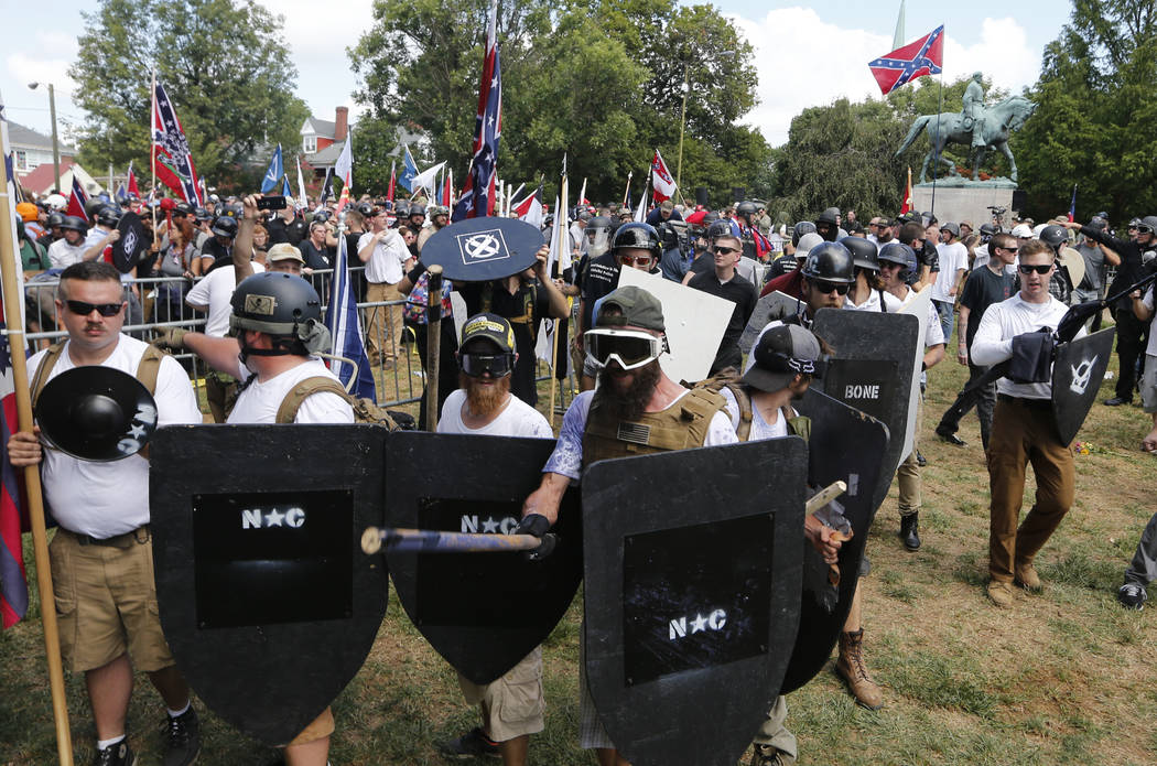 White nationalist demonstrators hold their ground as they clash with counter demonstrators in Lee Park in Charlottesville, Va., Saturday, Aug. 12, 2017. Hundreds of people chanted, threw punches, ...