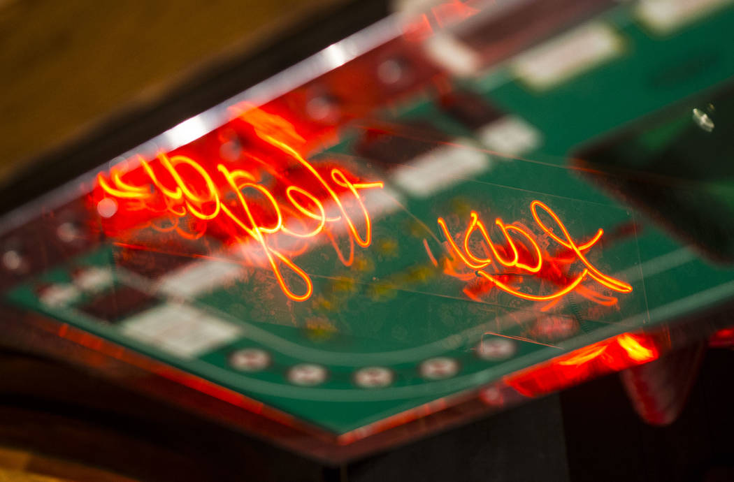 A neon Las Vegas sign is reflected in a Seven Eleven machine on display that was one of the first craps slot machines built for casino gaming at the Clark County Museum in Henderson on Wednesday, ...
