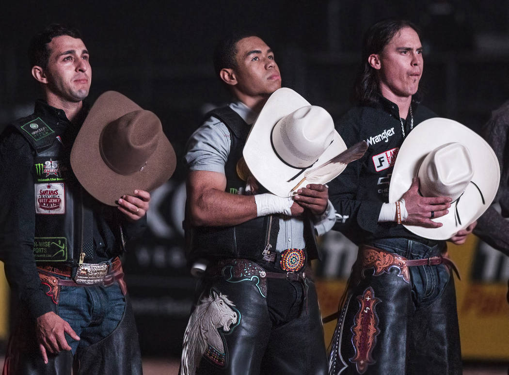Keyshawn Whitehorse, middle, listens the national anthem during the Professional Bull Rider's Last Cowboy Standing competition on Friday, May 4, 2018, at the Thomas & Mack Center, in Las Vegas ...