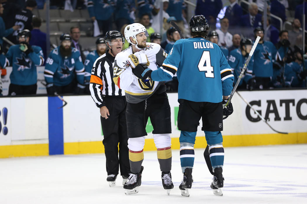 Vegas Golden Knights defenseman Shea Theodore (27) and San Jose Sharks defenseman Brenden Dillon (4) grab each other after a scuffle during the third period in Game 4 of an NHL hockey second-round ...