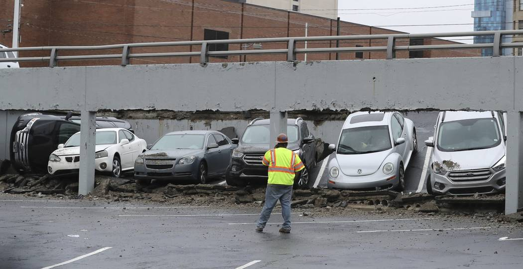 An official walks by the scene of a part of a parking deck that collapsed, Thursday, May 3, 2018, in Detroit. Deputy Fire Commissioner David Fornell says firefighters received a call about 10:20 a ...