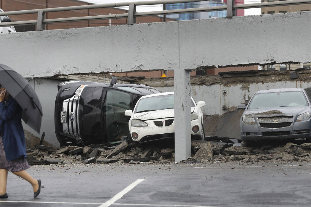 An official walks by the scene of part of a parking deck that collapsed, Thursday, May 3, 2018, in Detroit. Deputy Fire Commissioner David Fornell says firefighters received a call about 10:20 a.m ...