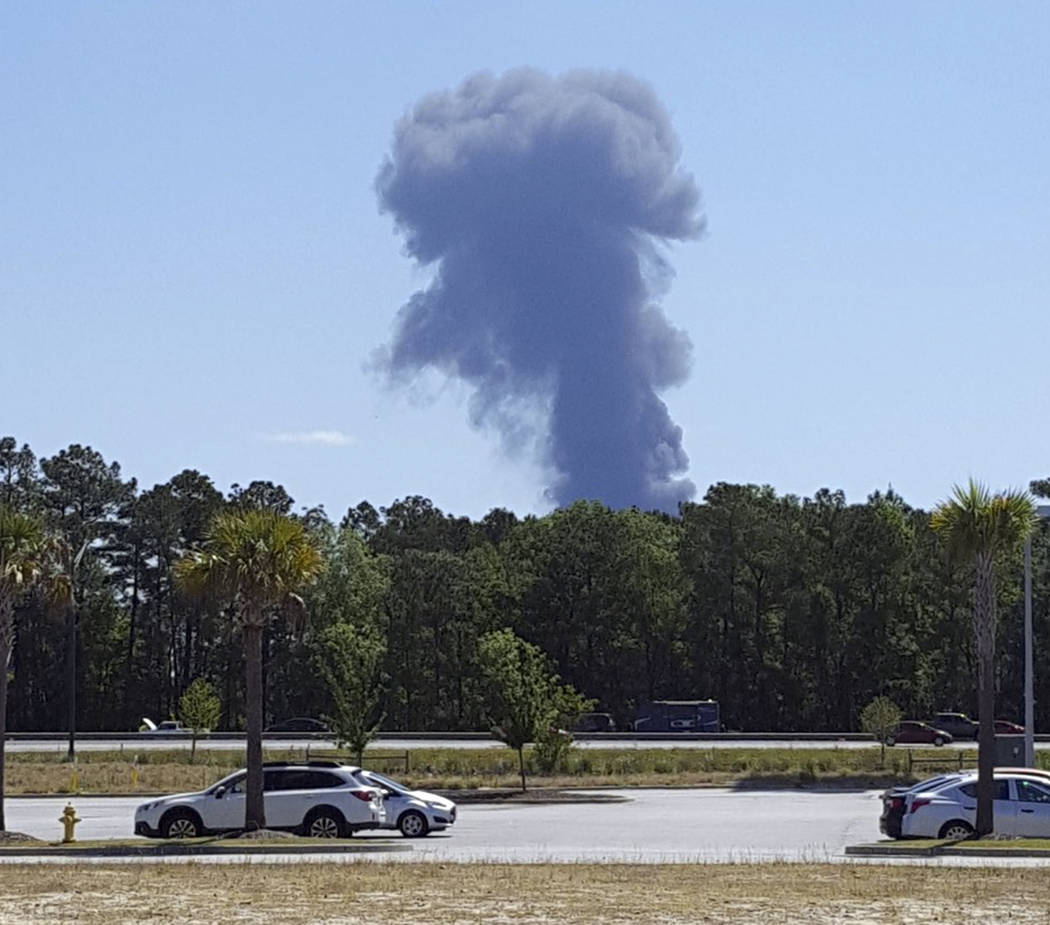 Smoke rises in the distant where an Air National Guard C-130 cargo plane crashed near an in Savannah, Ga., Wednesday, May 2, 2018, in this view from Pooler, Ga. (Minh Phan via AP)