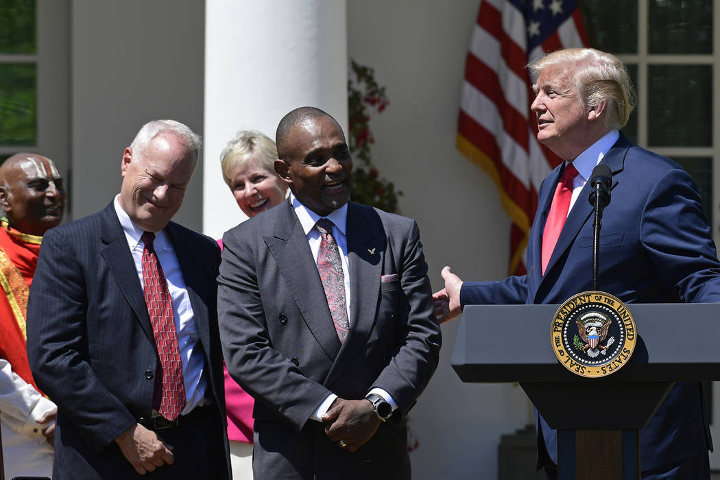 President Donald Trump, right, talks about Jon Ponder, second from right, from Las Vegas, and FBI Special Agent Richard Beasley, second from left, during a National Day of Prayer event in the Rose ...