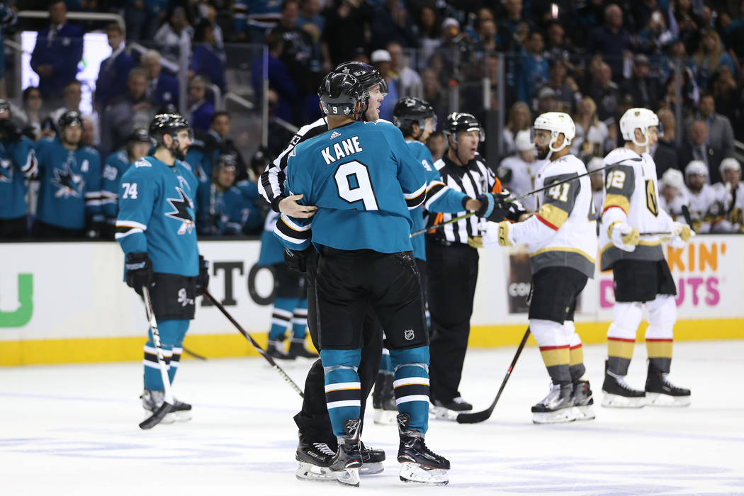 San Jose Sharks left wing Evander Kane (9) is hold back a by a referee after shuffle with the Vegas Golden Knights during the third period in Game 4 of an NHL hockey second-round playoff series at ...