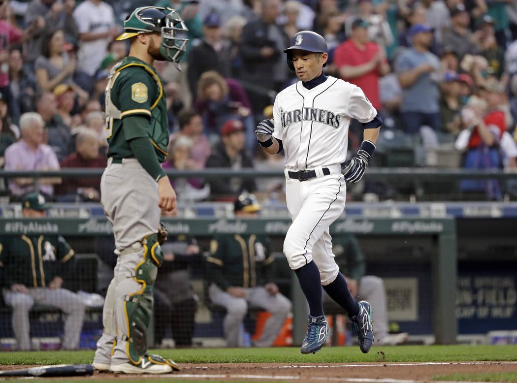 Oakland Athletics catcher Jonathan Lucroy waits as Seattle Mariners' Ichiro Suzuki scores during the third inning of a baseball game Wednesday, May 2, 2018, in Seattle. (AP Photo/Elaine Thompson)