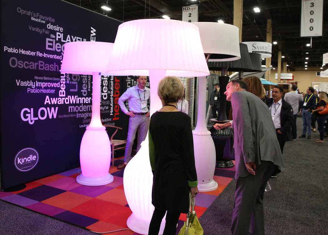 Conventiongoers check out giant outdoor lamps and outdoor heaters at KindleLiving's booth during the 2018 Hospitality Design Exposition and Conference on Wednesday, May 2, 2018, in Las Vegas. Bizu ...