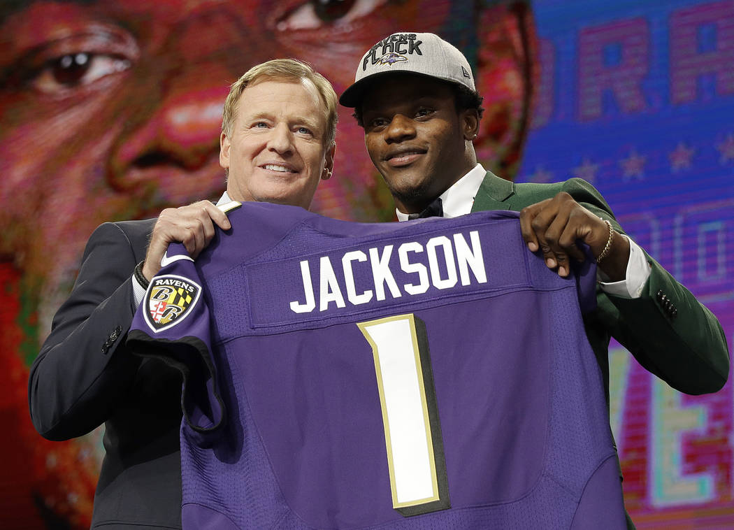 Commissioner Roger Goodell, left, presents Louisville's Lamar Jackson with his Baltimore Ravens jersey during the first round of the NFL football draft, Thursday, April 26, 2018, in Arlington, Tex ...