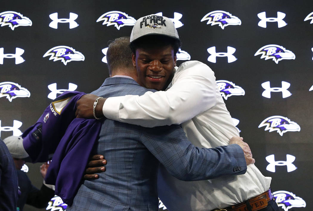 Quarterback Lamar Jackson, right, one of the Baltimore Ravens' first-round draft picks, hugs head coach John Harbaugh during an NFL football news conference at the team's headquarters in Owings Mi ...