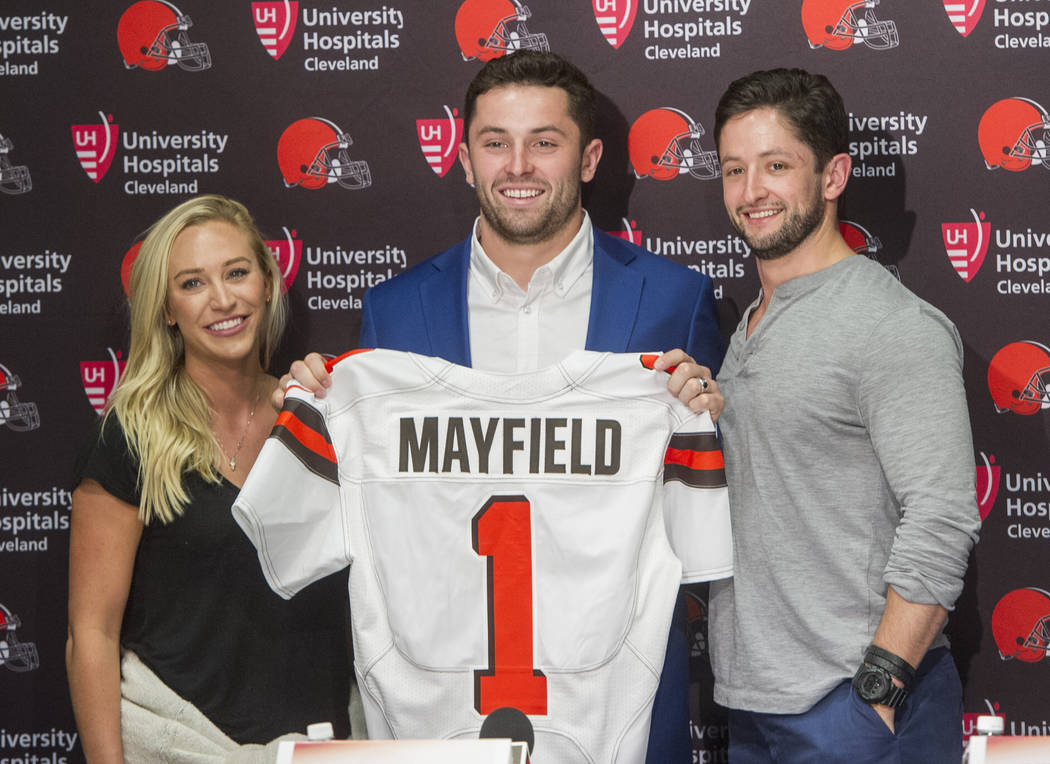 Cleveland Browns first-round draft pick Baker Mayfield, center, stands with his girlfriend, Emily Wilkinson, and brother Matt Mayfield after a news conference at the NFL football team's headquart ...