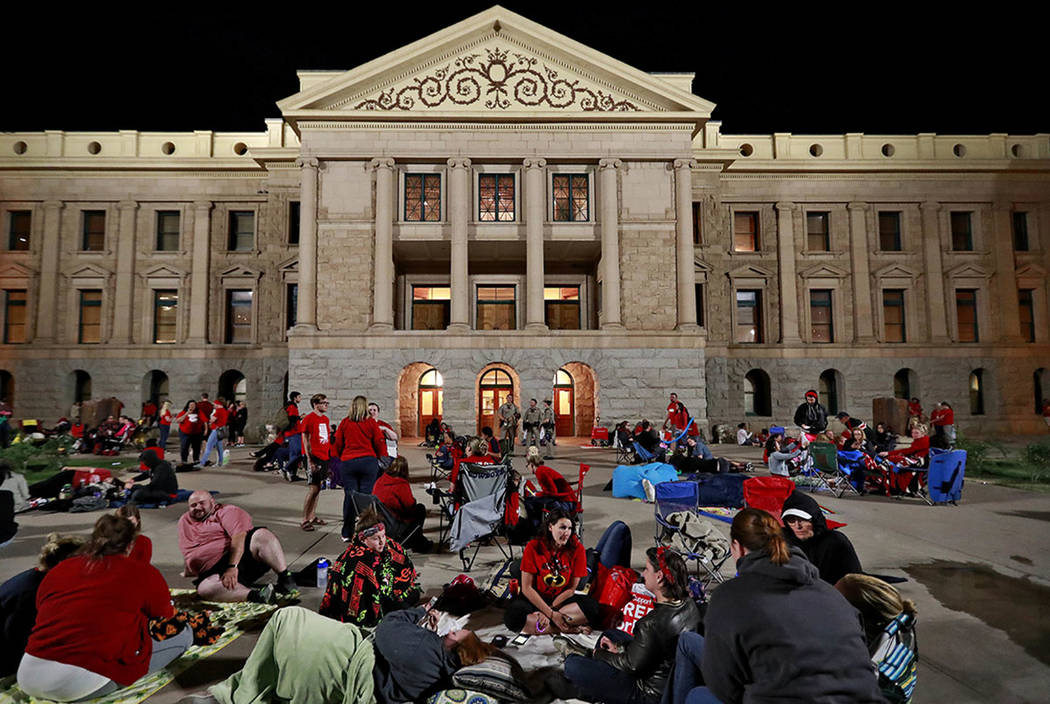 Teachers camp out as the Arizona legislature debates a budget negotiated by majority Republicans and GOP Gov. Doug Ducey Thursday, May 3, 2018, at the Capitol in Phoenix. (AP Photo/Matt York)
