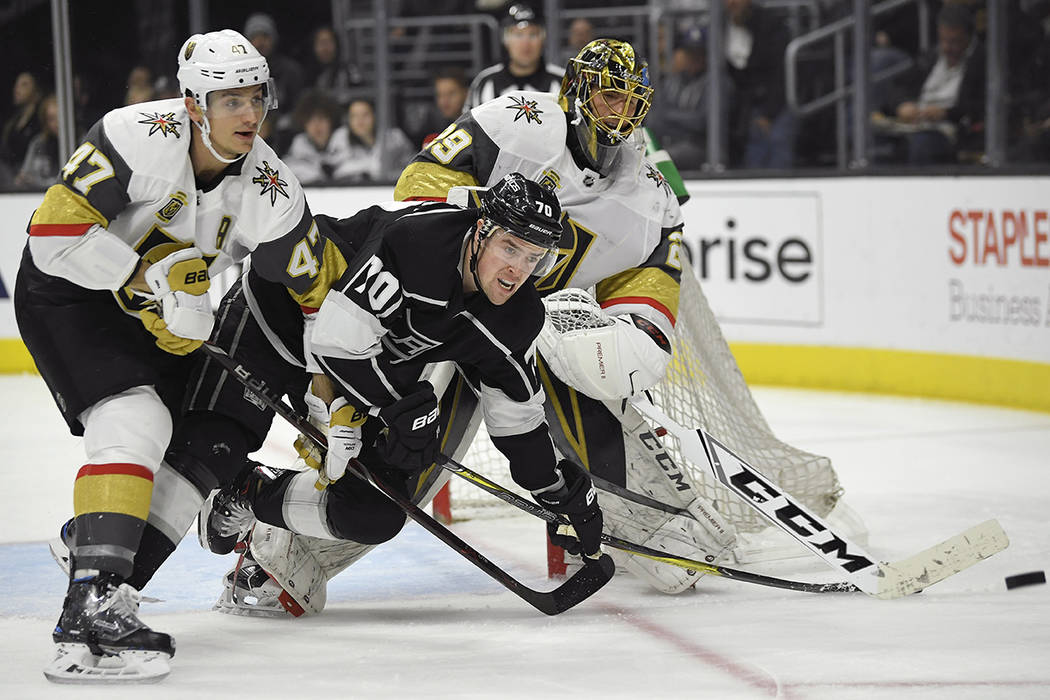 Vegas Golden Knights goaltender Marc-Andre Fleury, right, shoots the puck away as defenseman Luca Sbisa, left, of Italy, battles with Los Angeles Kings left wing Tanner Pearson during the second p ...