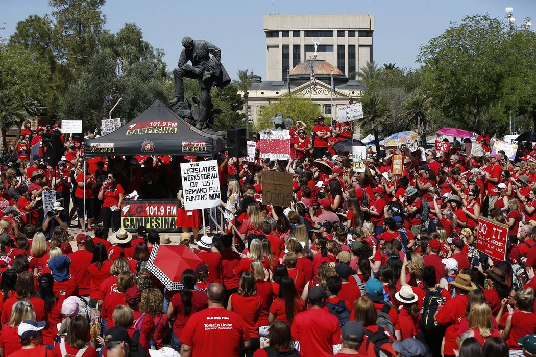 With the Arizona Capitol in the background, thousands of teachers continue to protest Thursday, May 3, 2018, in Phoenix. After an all night legislative budget session the legislature passed the ne ...