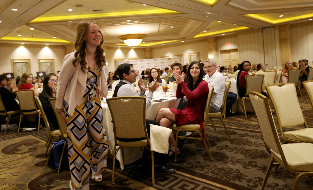 Caitlin Gaddis, of Spring Valley High School, goes up to receive her award for Best Feature Photo at the Las Vegas Review-Journal High School Journalism Awards at the Suncoast in Las Vegas Monday, ...