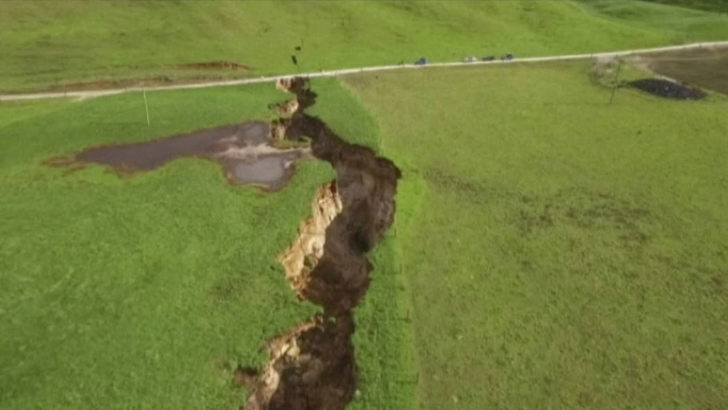 This image made from the May 2, 2018 video shows huge sinkhole on farm in Rotorua, New Zealand. A spectacular sinkhole the length of two football fields and the depth of a six-story building has ...