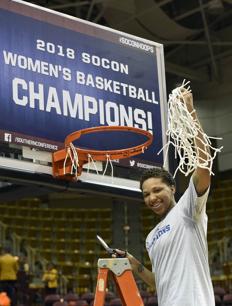 Mercer's Kahlia Lawrence holds a basketball net in the air after she cut it from the rim to celebrate her team's win over East Tennessee State in an NCAA college basketball game for the Southern C ...