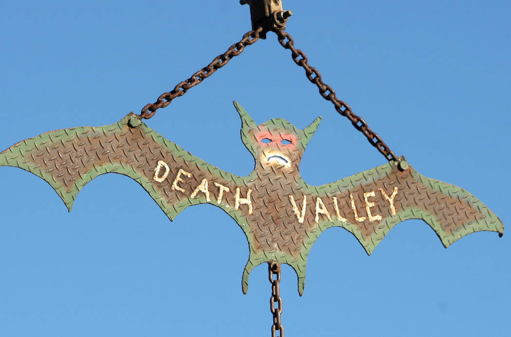A bat icon cut from steel hangs from a pole at the Saline Valley Hot Springs in Death Valley National Park. (J. Emilio Flores)