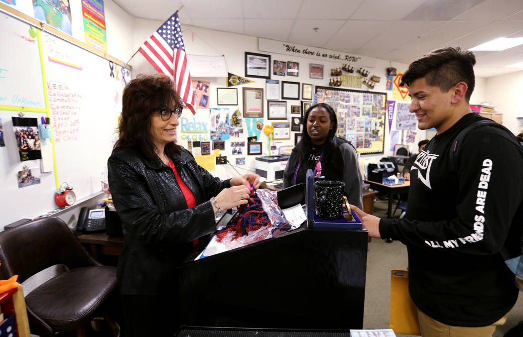 Clark High School teacher Luanne Wagner gives a graduation cord to senior Brandon Cera as Blane Cheru looks on before a meeting of the KEEN Club Wednesday, May 2, 2018. Wagner is the club advisor ...